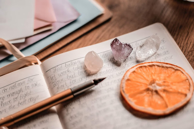 A collection of items: pen, journal, pastel-colored crystals and envelopes.