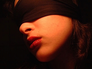 A woman blind folded and held hostage