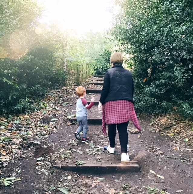 Mum and son walking through a wood