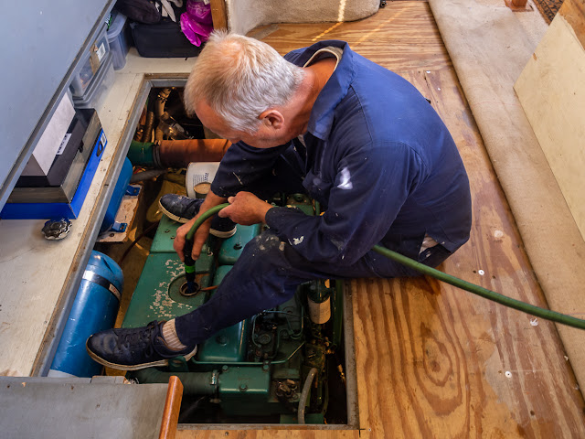 Photo of Phil flushing the heat exchanger with clean water before filling it with the water/antifreeze mixture