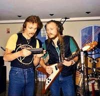Rudolf e Michael em 1985 em estúdio. Rudolf segura algo que parece um gravador e Michael, com fone de ouvido ligado ao gravador, toca sua guitarra flying V.