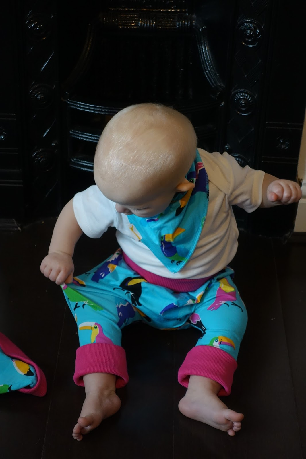 Baby is pulling at the leg of Funky Giraffe Trousers