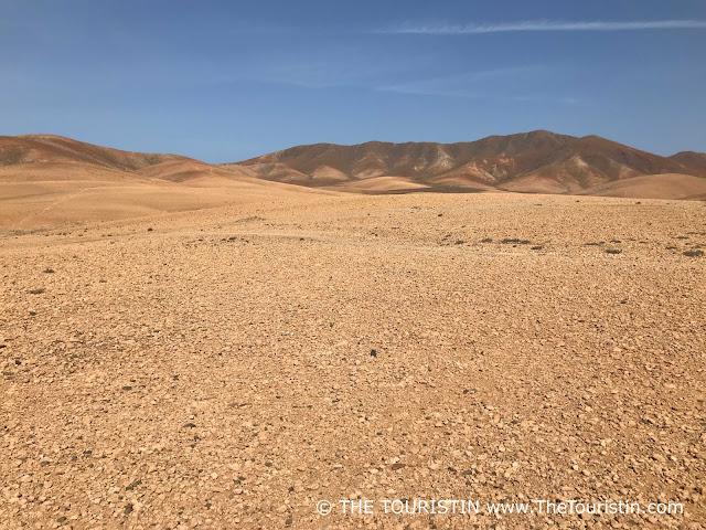 Wide arid landscape under a blue sky.