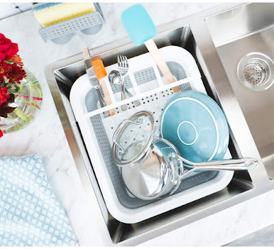 a full dish rack sitting in the sink