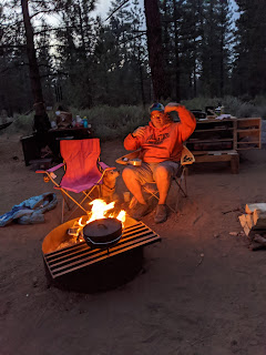 Christopher Sean Harris sitting at a campfire and pointing at a pine cone.