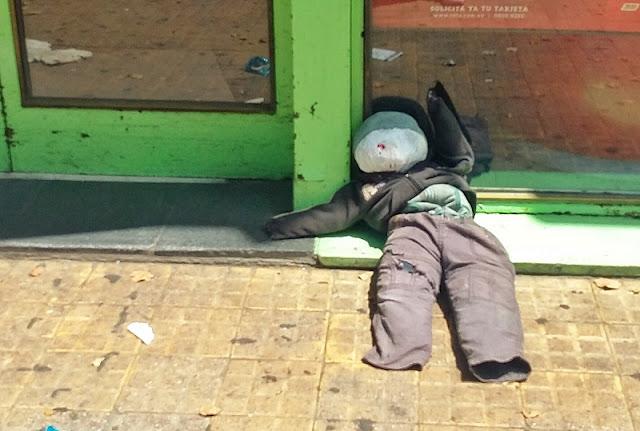 Imagen de un judas de trapo tirado en la puerta de un comercio