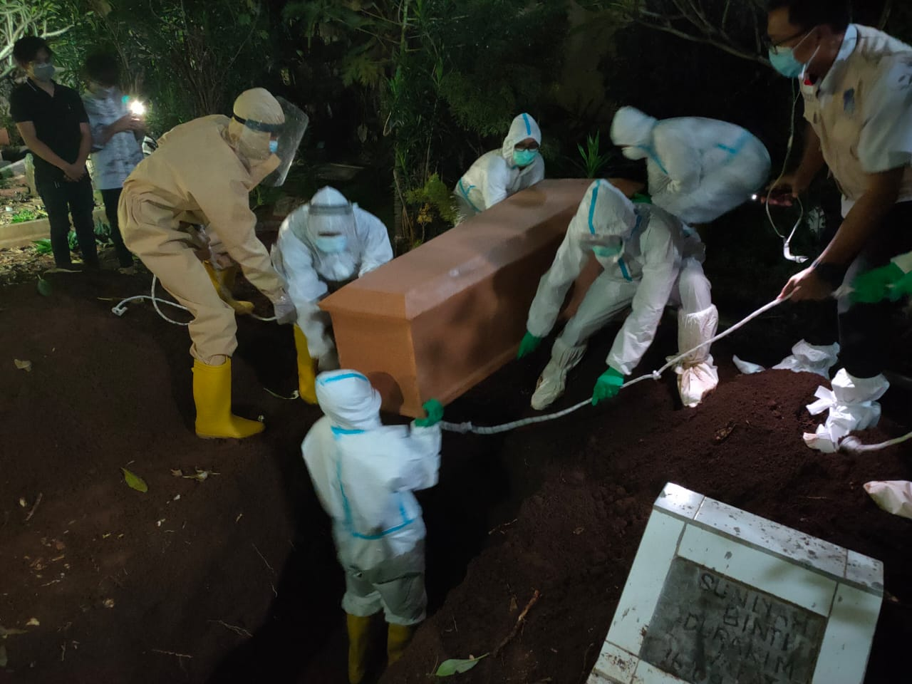 Babinsa Koramil 410-06/Kedaton Serda Andreswan yang tergabung dalam Tim evakuasi Satuan Tugas Percepatan Penanganan Covid-19 Kota Bandar Lampung, melaksanakan prosesi pemakaman jenazah konfirmasi Positif Covid-19