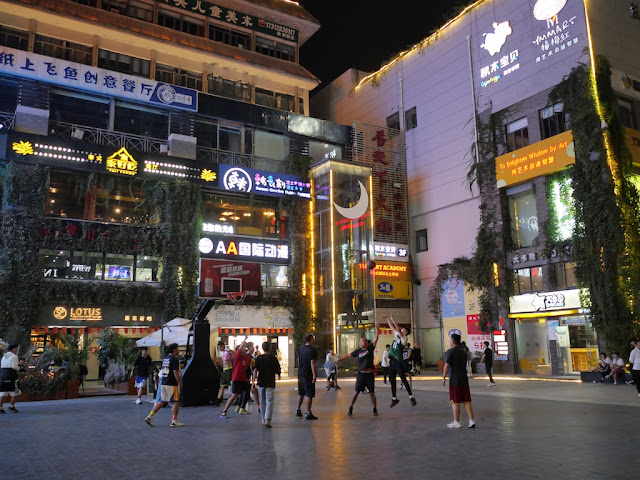 people playing basket in front of a shopping center