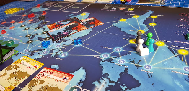 Pandemic gameplay board layout with pieces pawns and cards