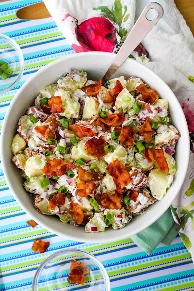 Top view of red potato salad with bacon in a white bowl on a blue and green striped background.