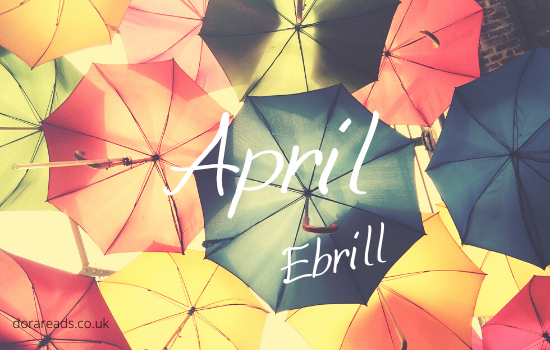 'April - Ebrill' with a bunch of umbrellas in the background. Just, y'know, floating of their own volition. As they do when you need an artsy background.