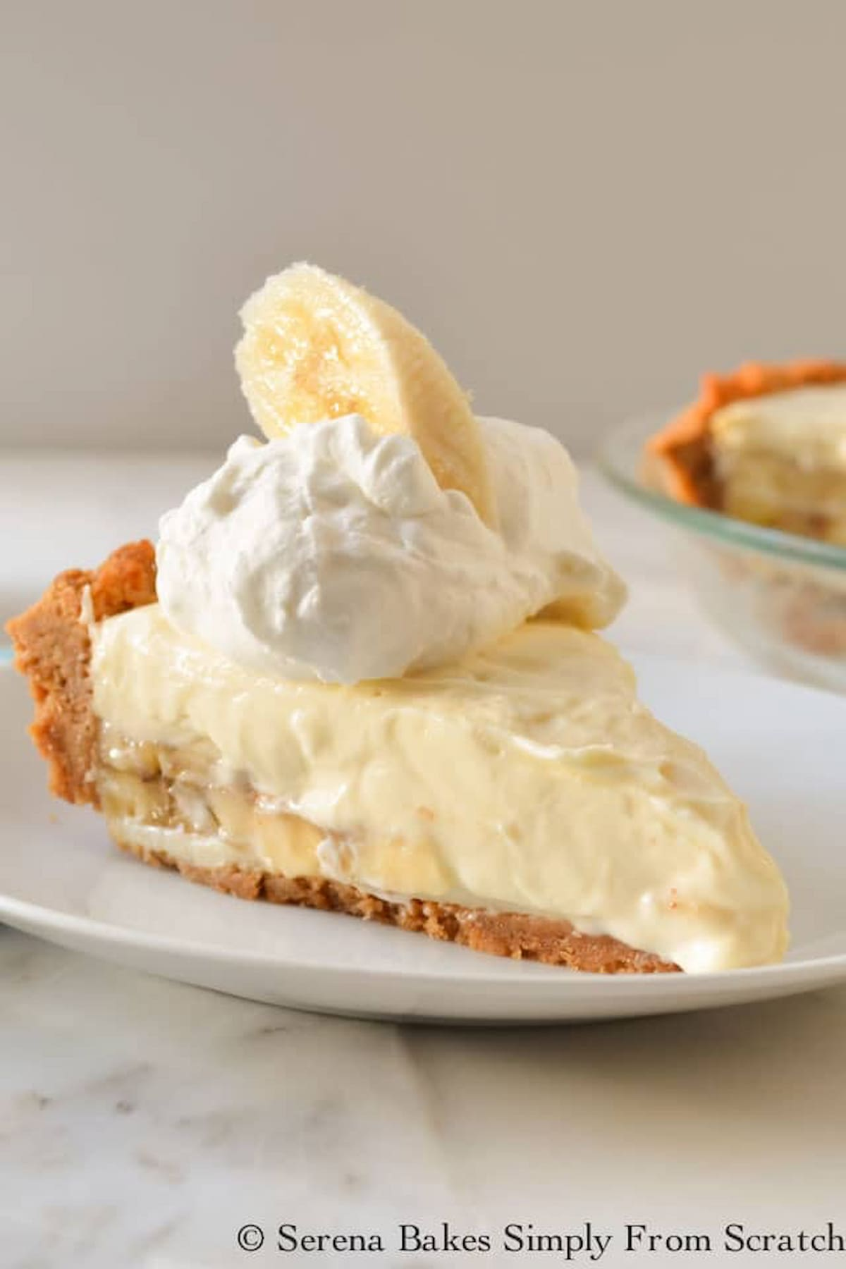 A slice of Banana Pudding Cheesecake with a graham cracker crust topped with whipped cream and a slice of banana on a white plate with a  banana pudding cheesecake in a pie plate in the background.