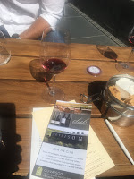 Photo of glass of wine at outdoor wine tasting at Cuvaison winery in Napa. https://trimazing.com/