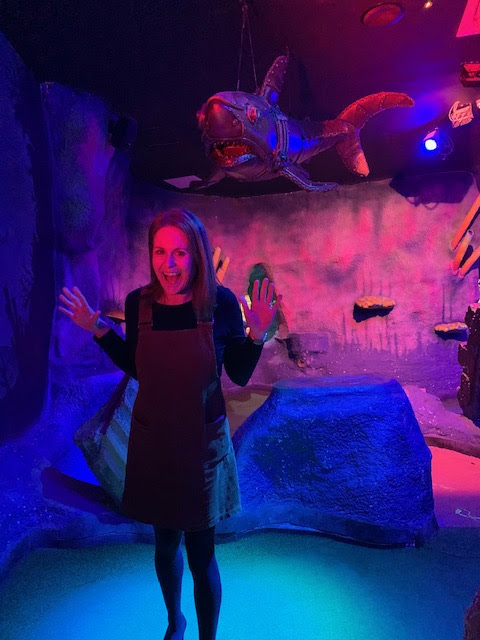 Woman pretending to be scared of shark on crazy golf course