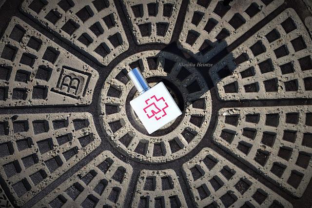 Zdjęcie flakonu perfum Rammstein Kokain na studzience kanalizacyjnej