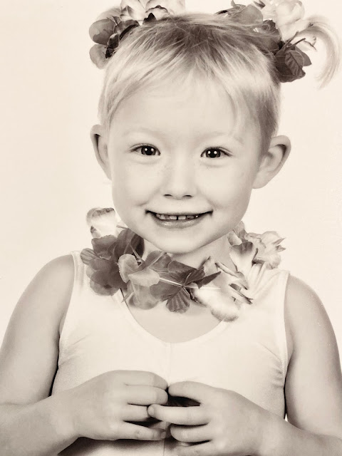 A black and white head shot of little with a flower garland round her neck and in her hair