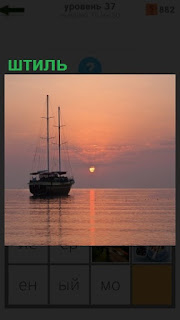 на море в штиль стоит яхта без парусов, одни мачты