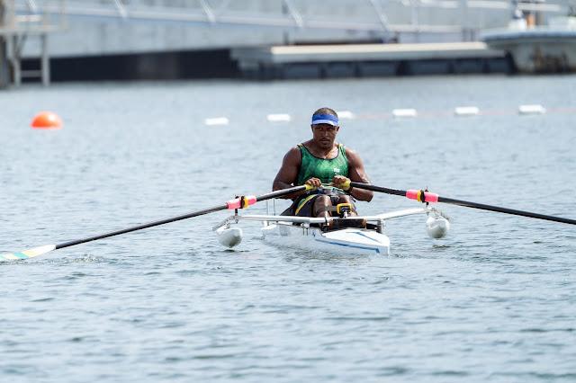 Renê Campos Pereira em um barco branco, com camisa verde e viseira azul em ação nos Jogos Paralímpicos