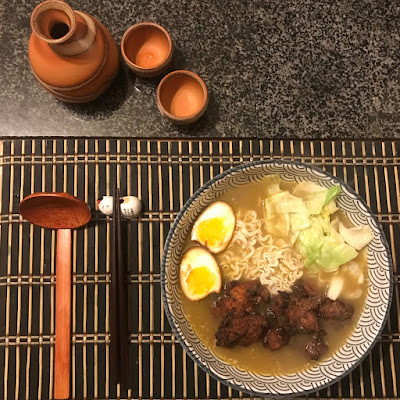 A bowl of ramen, with chopsticks and a wooden spoon beside it.
