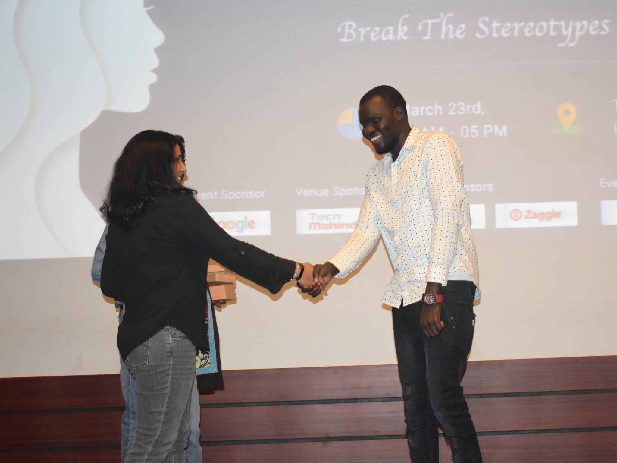 Kose shakes hand with woman at stage
