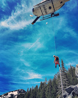 A sheriff's office emergency medical team member is lowered down from a medevac helicopter.