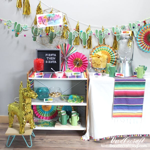 Gold tassels and gold llama pinata with brightly colored hanging fans, cactus mugs, letterboard and other party supplies from Oriental Trading.