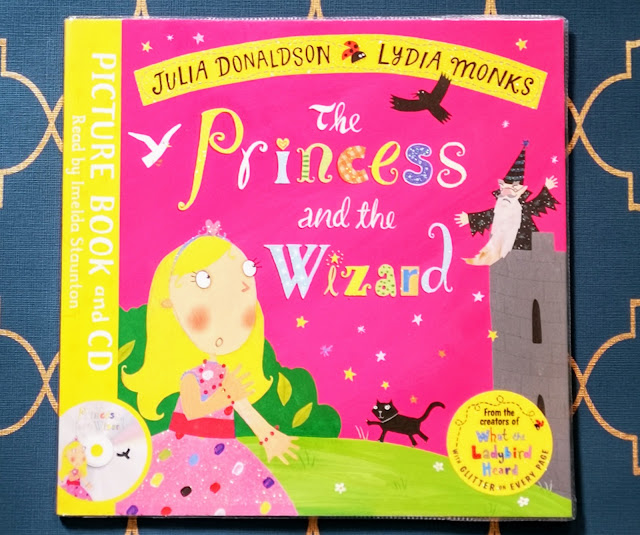 Image of the front cover of The Princess and the Wizard by Julia Donaldson and Lydia Monks. The cover features the book title and authors names alongside an image of a princess hiding in a bush and a wizard high in a castle. The cover also features an image of a crow, dove and cat. The cover is bright pink and yellow and also an emblam indicating that this version comes with picture book and CD and that it has been created by the same people that made What The Ladybird Heard.