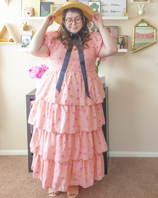 An outfit consisting of a straw boater hat with a black ribbon tied under the chin, and a pastel pink tiered off-the-shoulder floral maxi dress with short puff sleeves.