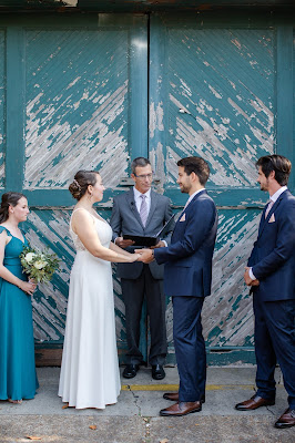 bride and groom holding hands in front of Artisan Alley