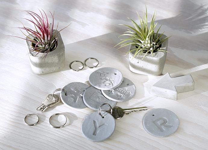 2 Aufsitzerpflanzen in kleinen Betonvasen, runde Schlüsselanhänger mit geprägten Buchstaben