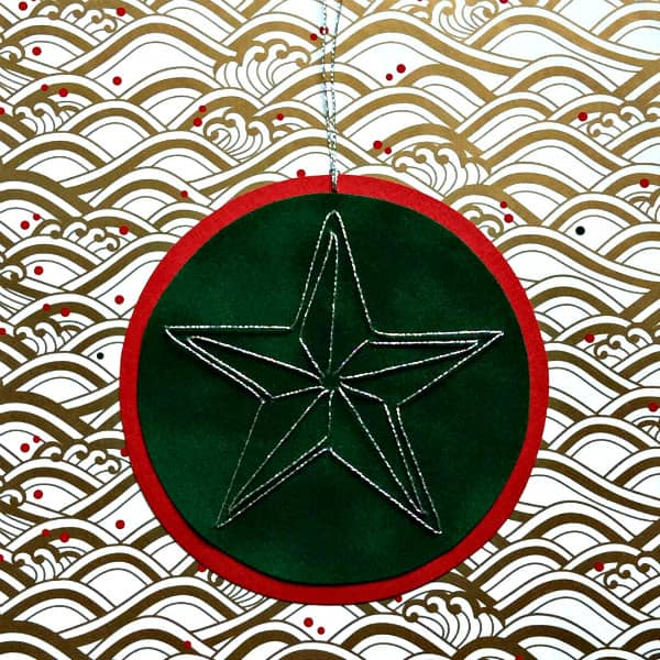stitched silver star on circular ornament displayed on patterned paper