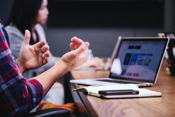 pessoa sentada à mesa em frente a um caderno e smartphone, aparecem suas mãos gesticulando