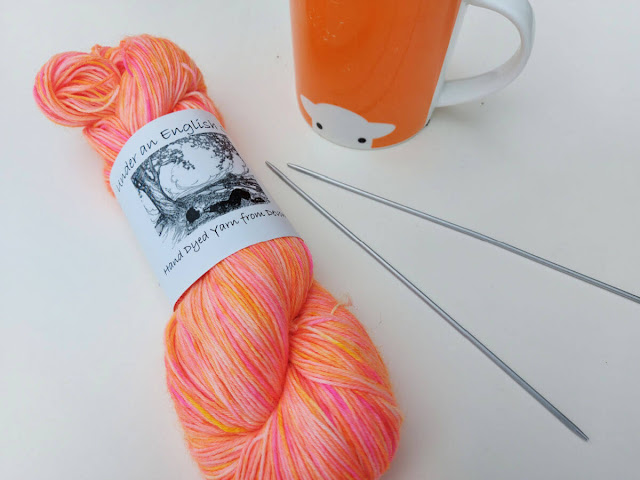 A skein of orange hand-dyed yarn is lying on a cream background next to an orange mug of tea and two double pointed needles