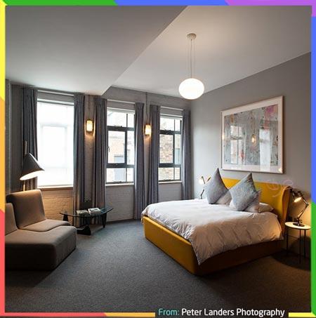 غرفة نوم مع ستارئر رمادي ووسائد صفراء