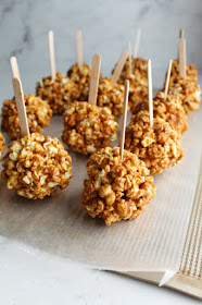 freshly formed caramel apple popcorn balls on wax paper with popsicle sticks inserted