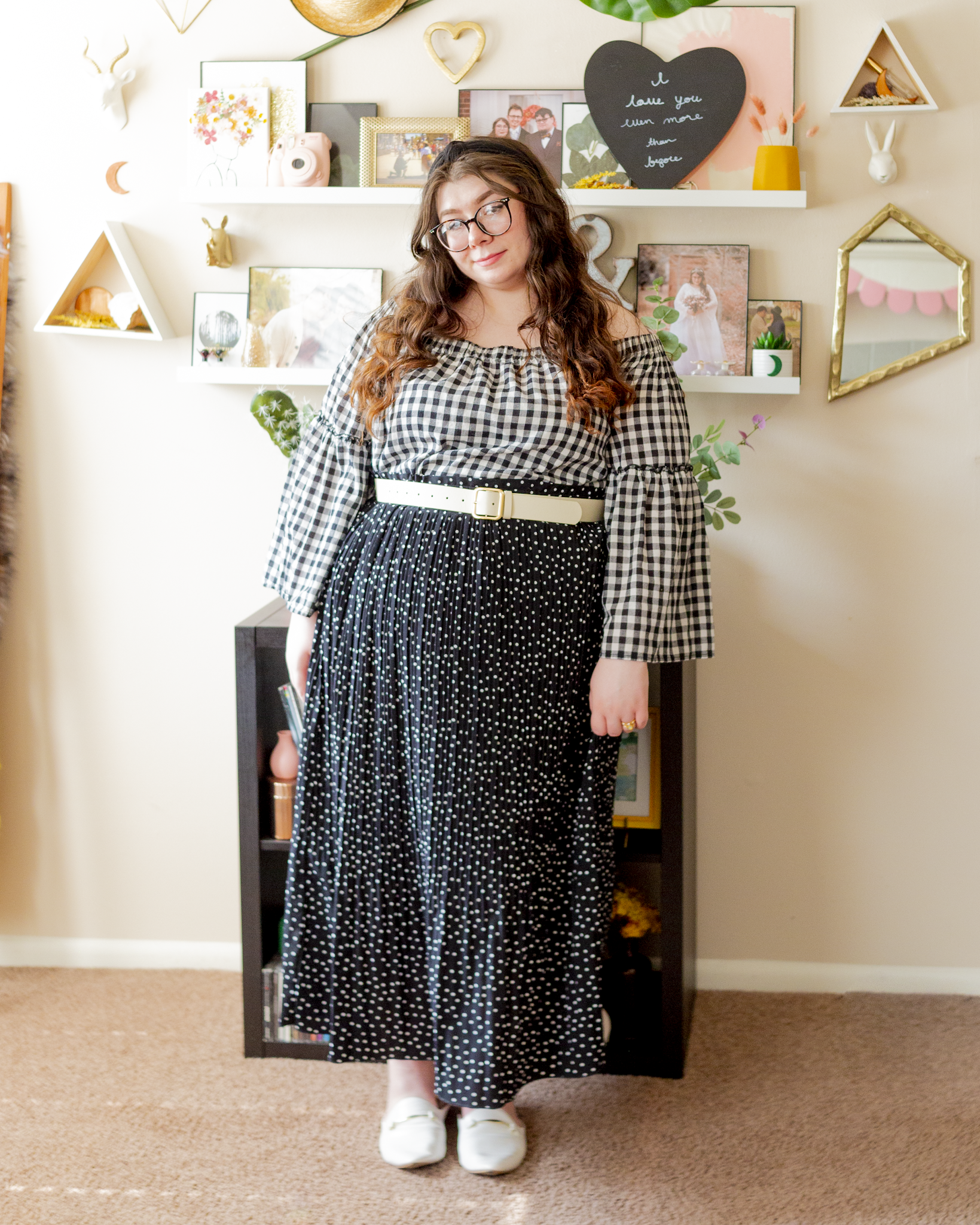 An outfit consisting of a black on white gingham bardot top with angel sleeves tucked into a white on black microdot pleated midi skirt belted with a white belt with a minimal gold buckle and white faux croc mules with a minimal gold buckle detail.