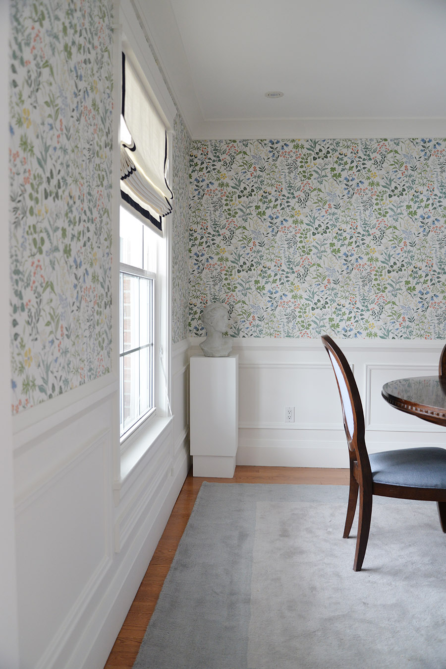 traditional dining room, oval back chairs, head planter, pedestal, Scandinavian floral wallpaper, moulding, wainscotting