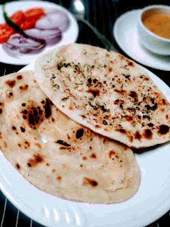 Serving two butter naan dal onion tomato in background