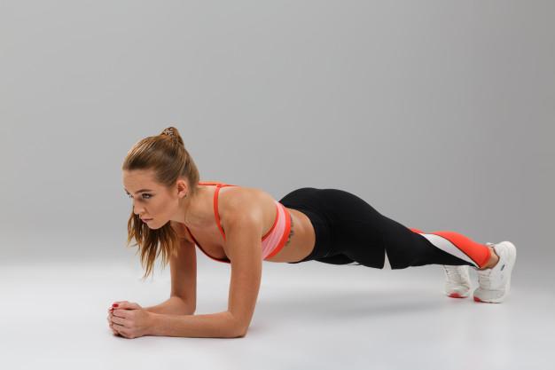 mulher fitness fazendo exercício de prancha em casa