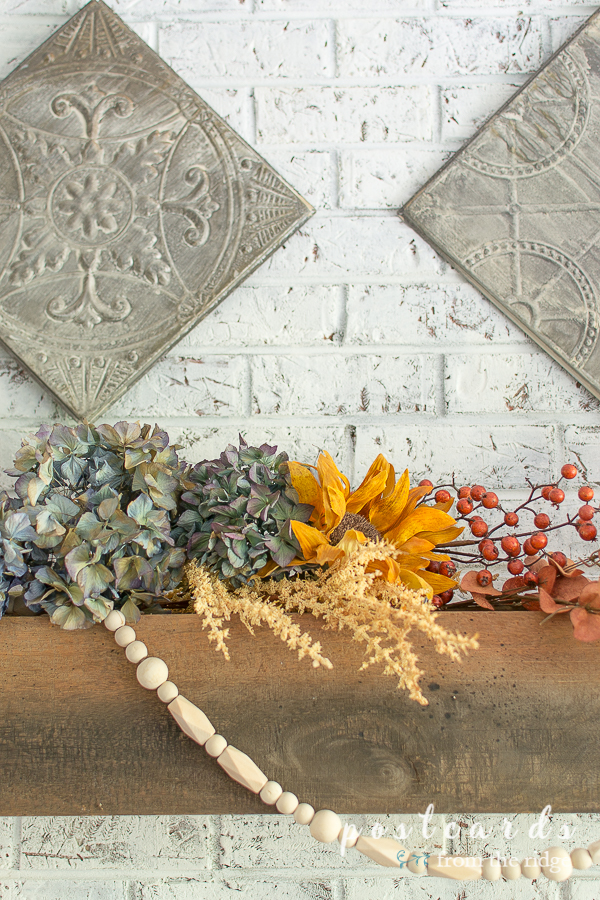 dried hydrangeas, sunflower, and wood beads on wood beam mantel
