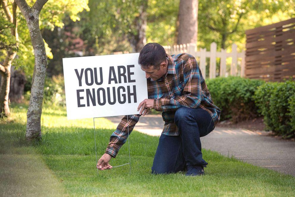 man kneeling before a signpost