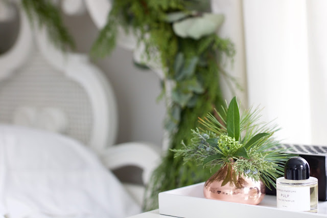 vintage white cane headboard with evergreen and eucalyptus garland copper bud vase byredo pulp perfume