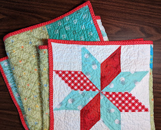 Quilt is folded so corner star shows along with part of the green back and the red binding