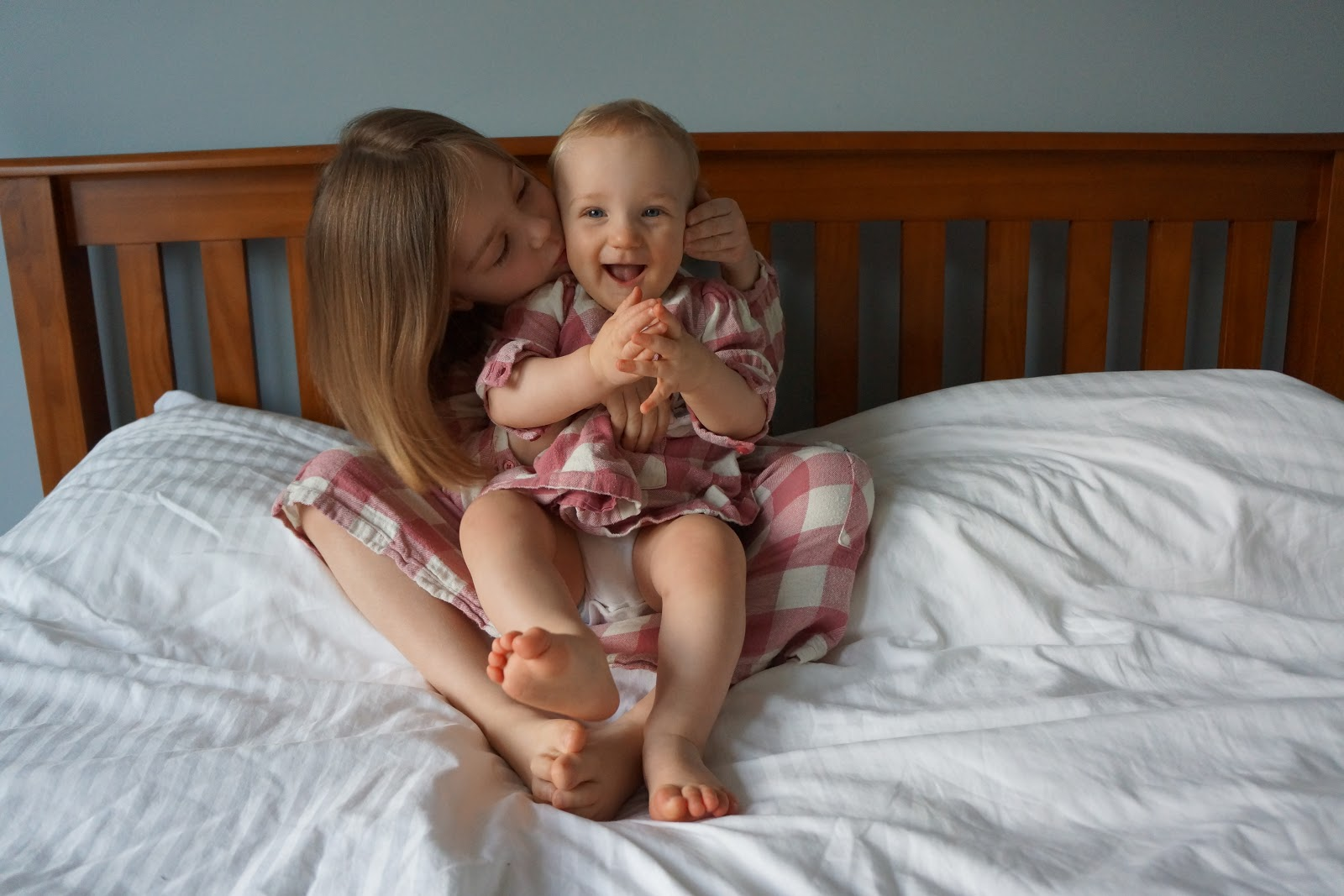 baby and sister in matching dresses kissing