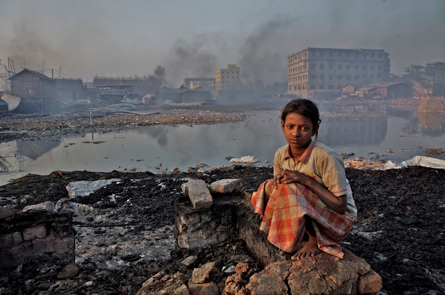 A young girl sits on broken wall inside an informal glue factory where workers process waste leathers to make glue in Hazaribagh area near Buriganga river in Dhaka (Bangladesh). UNICEF Photo.