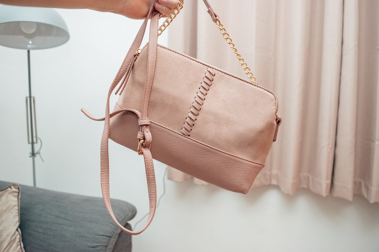 A pink cross body bag with a plait design down the middle and gold chain belted strap.