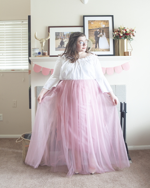 An outfit consisting of an off the shoulder white ruffle and bell sleeve blouse tucked into a pink tulle maxi skirt and nude heels.