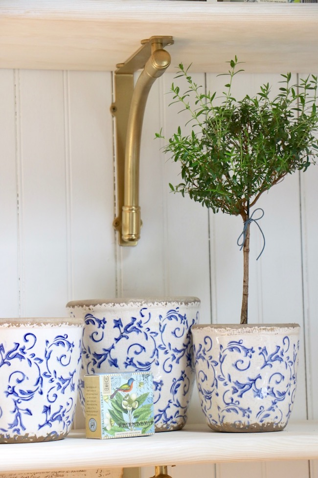 Gold painted shelf brackets add French Country elegance to open shelves