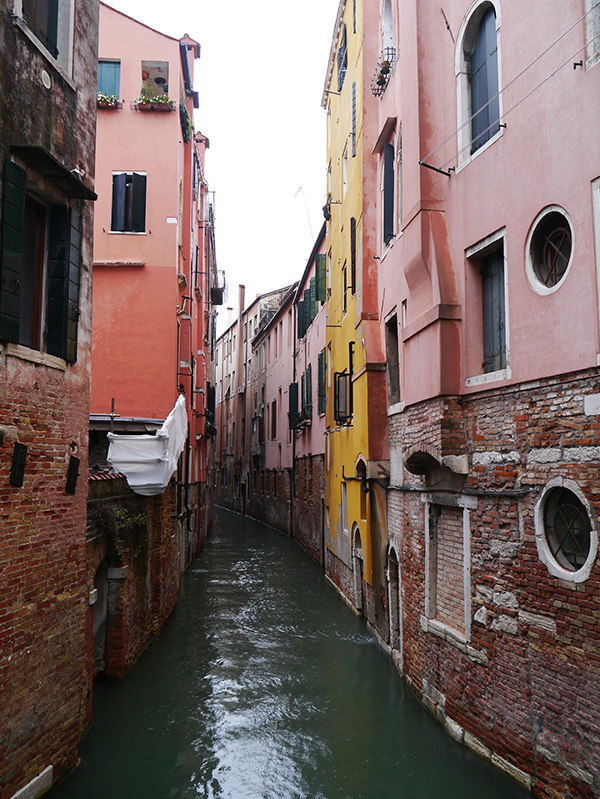 Narrow canal with pink and coral buildings in Venice, Italy