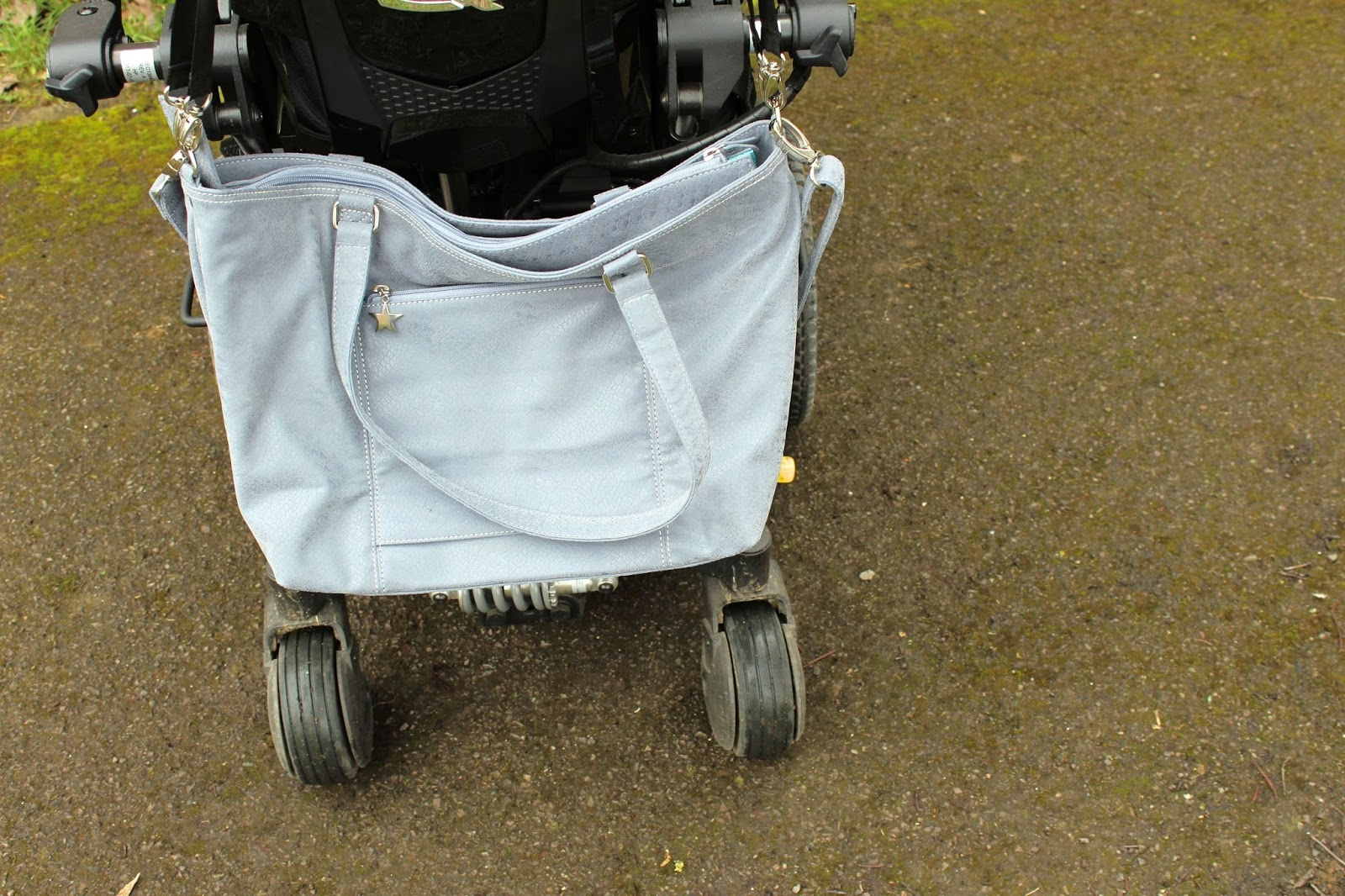 A large grey handbag is visible on the back of the powerchair.